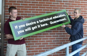 Metal fabrication/welding students Zach Green (left) and Colby Ormsby adjust new signage at Region Ten Technical High School in Brunswick.