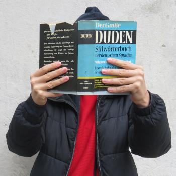 Symbolbild Person mit historischem Duden; Bild: ufuq.de