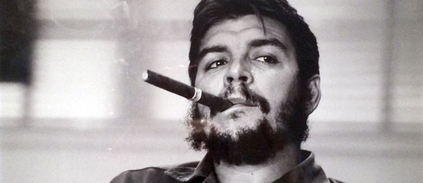 A photograph in the public domain of Che Guevara looking thoughtful and smoking a cigar.