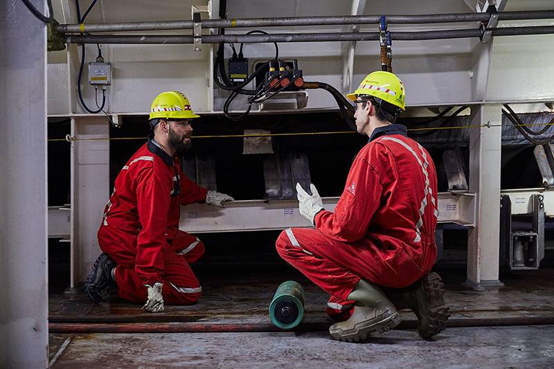 Two seafarers in red jumpsuits work on a ship