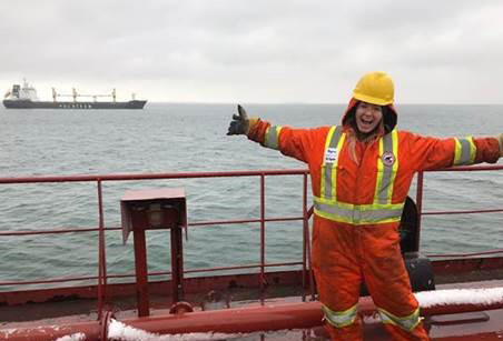 Samantha McPherson standing on board a Canadian ship with her arms outstretched