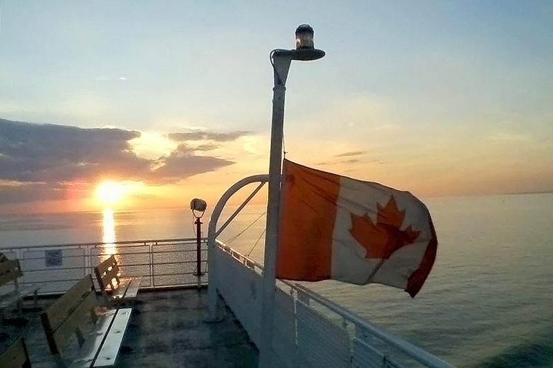 Canadian flag flying in front of a sunset