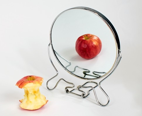 Apple core reflected as whole apple in mirror