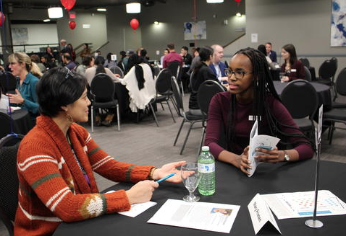 Student at table speaking with alumna