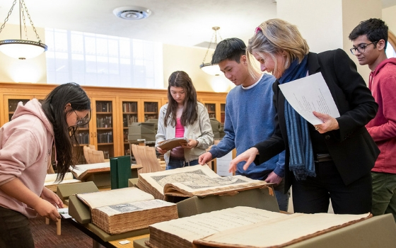 students and professor looking at old texts