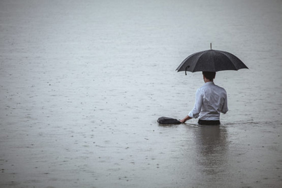 Guy with umbrella in waste-high water