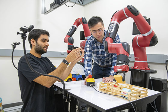 Researchers with robot arms