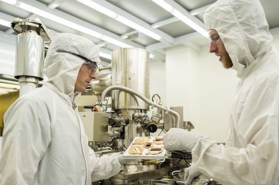 Two researchers in cleanroom holding materials/Photo: Ker Than