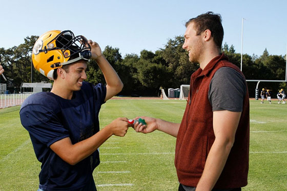 Research assistant William Nehring hands mouthguard to Menlo School sophomore J.P. McKenney (Paul Sakuma)