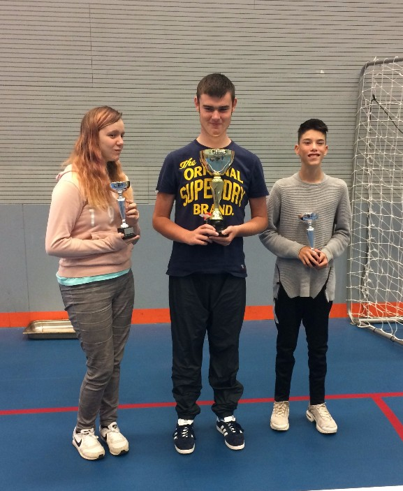 Champions smiling with their trophies from the Boccia Championships.
