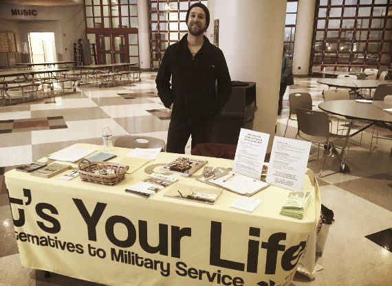 Table set up in school cafeteria with info on alternatives to military service