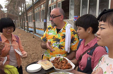 "Howie Southworth sharing a luau on Bo'ao Beach in ""Sauced in Translation"" episode 4 in Hainan, China. (Howie Southworth)"