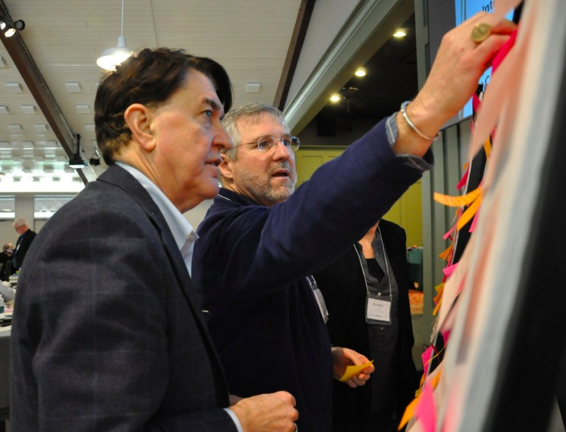 image description: two bishops wearing dark suits examine a board covered with sticky notes
