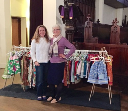 image description: two women smile in front of a rack of handmade colorful girls' dresses