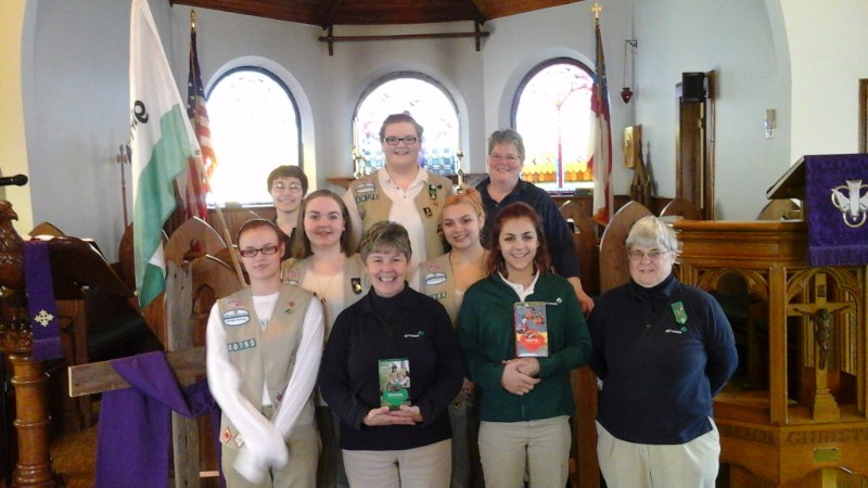 image description: girl scouts and their adult leaders smile in the chancel of St. Ann's Church