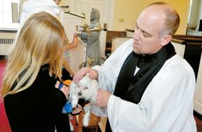 image description: The Rev. Jon White blessing a small dog