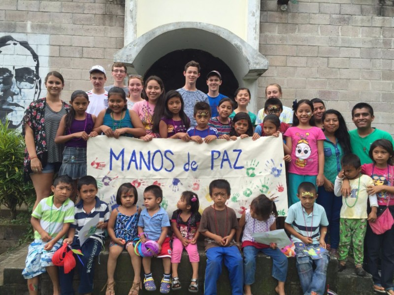 """image description: A group of Savadoran children and youth stand with a small number of American youth. They are holding a handmade sign, covered with their handprints, reading """"Manos de Paz"""" (Hands of Peace)"""