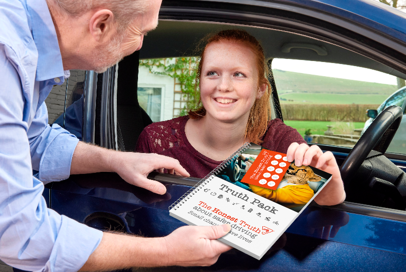 A driving instructor shows a learner driver road safety information
