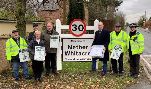 Villages and the PCC lining up at the Nether Whitacre sign at the village entrance with crime prevention signs