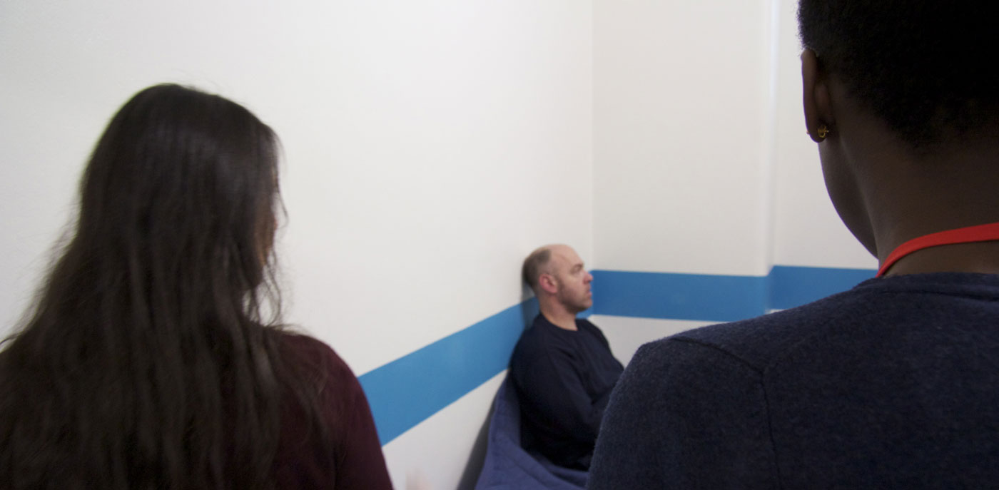 Two Independent Custody Visitors entering a police cell to talk to a detainee