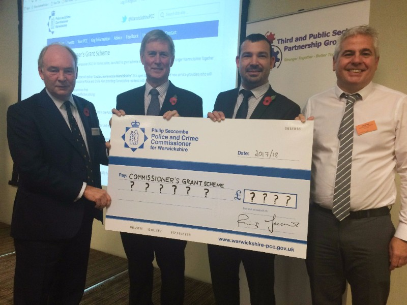 Philip shows off a giant cheque for good causes with delegates at the conference