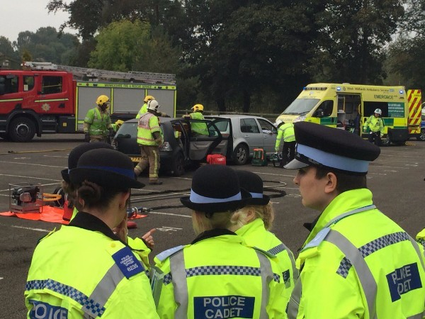 Police cadets watch a demonstration by fire and ambulance service staff at a mock road crash
