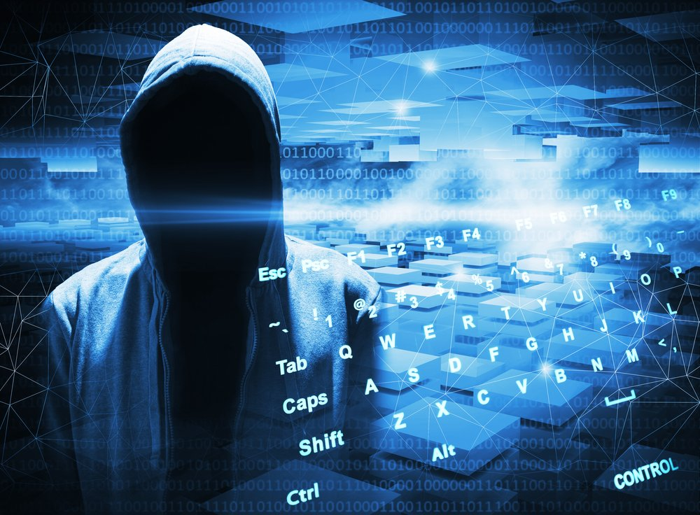 A hooded figure in front of a keyboard illustrating cyber crime