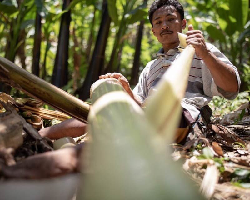 man stripping bamboo for sustainable bags