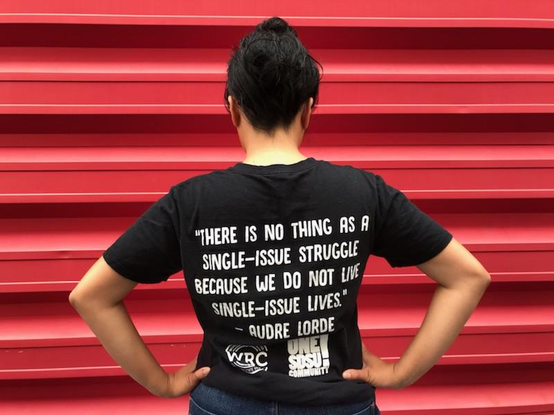 """A woman stands in front of a red shipping container with her back to the camera. Her shirt reads """"There is no thing as a single-issue struggle because we do not lead single-issue lives.""""—Audre Lorde"""