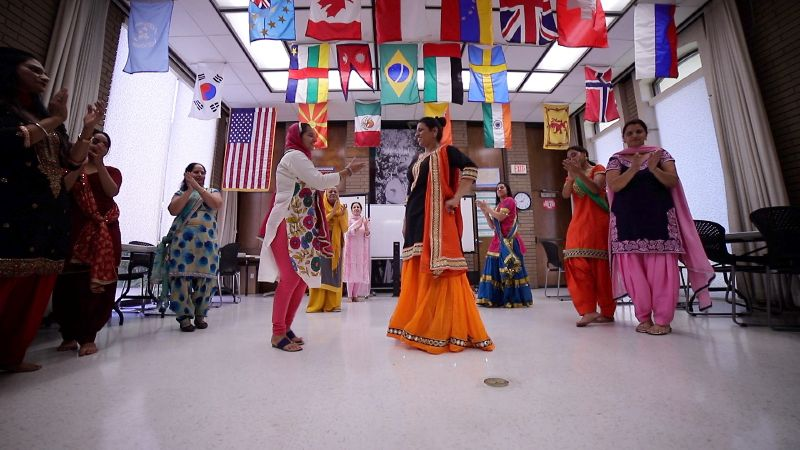 A group of women dressed in traditional South Asian clothing dance in a room underneath a ceiling hung with flags from many different countries.