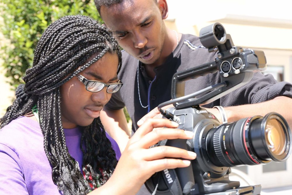 Two young people look into a camera.