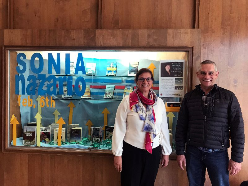 Sonia Nazario stands next to Shasta College History Instructor Chris Rodriguez, and a display of books selected that relate to themes of immigration and journalism.