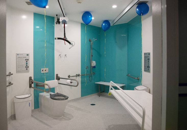 Image description: Changing Places toilet facility with handrails each side of toilet, a hoist for lifting people above the toilet and an adjustable adult-sized change table. 4 balloons with streamers attached are hanging from the roof.