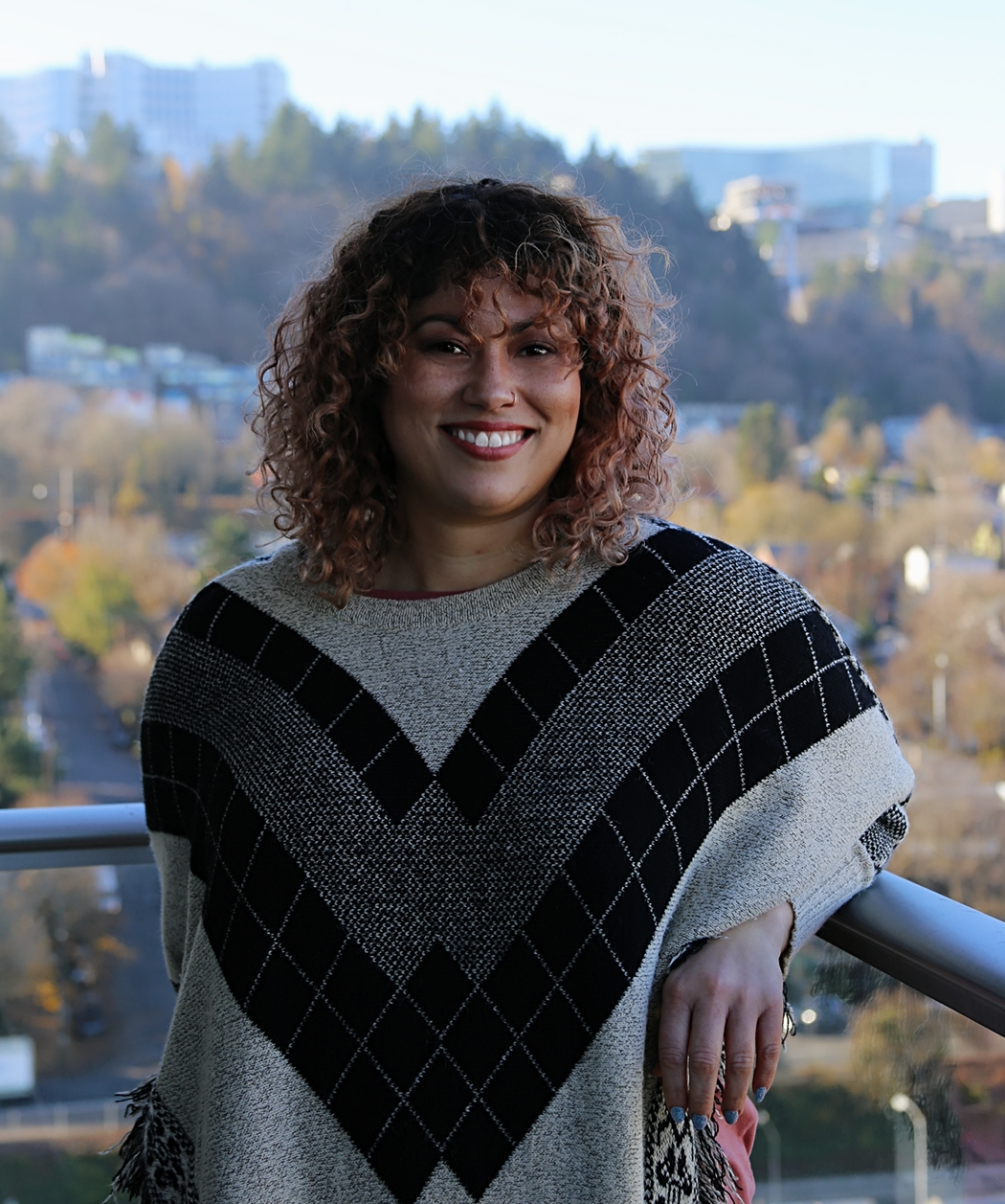 Photo of our Member Yeruwelle in front of a landscape of trees and city buildings. She is wearing a patterned black and gray sweater and smiling.