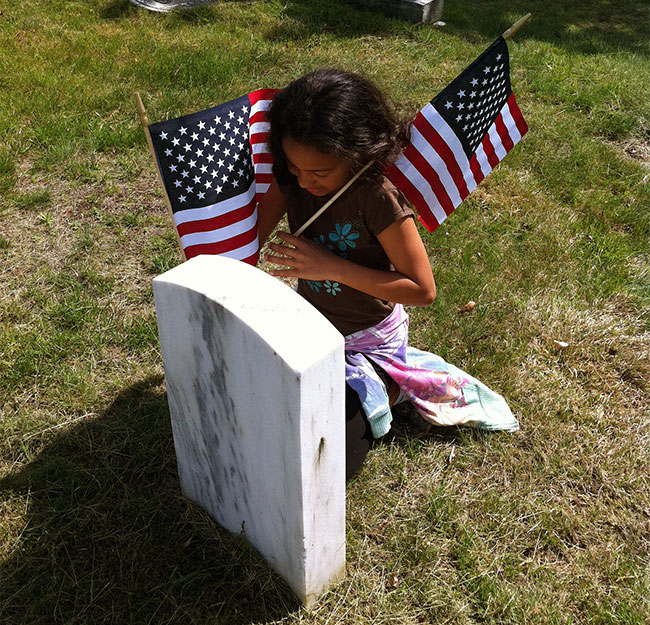 girl placing flag at gravestone