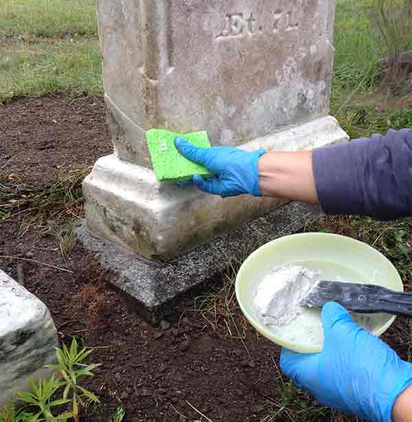 Touching up a repair in a marble headstone