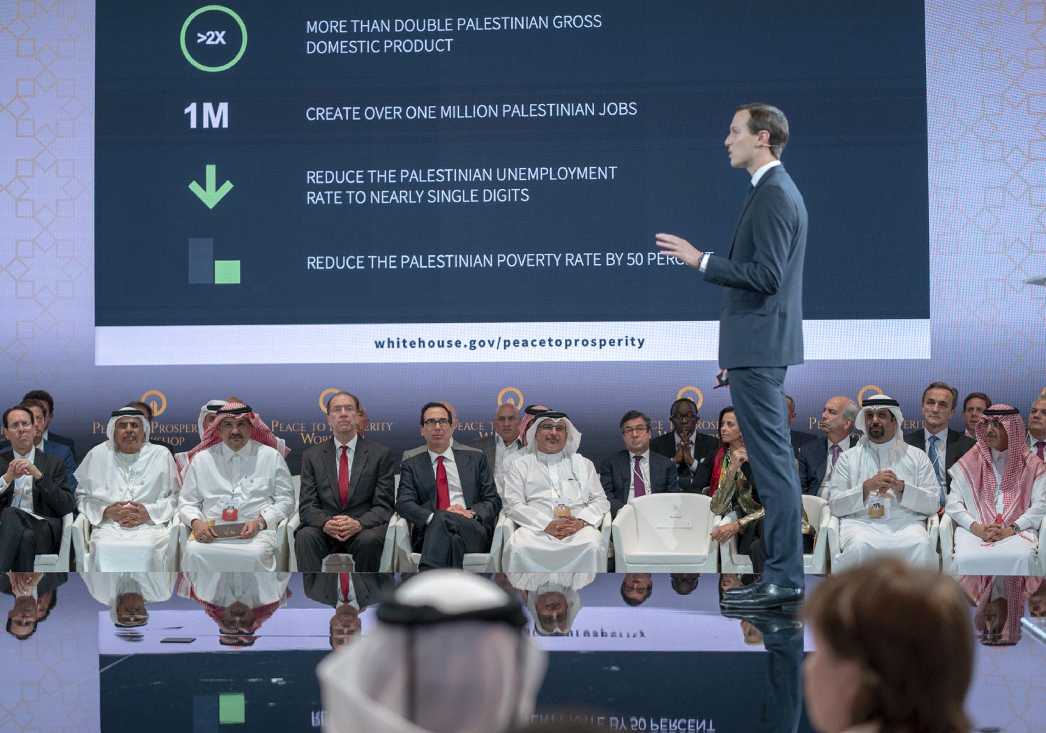 "U.S. Treasury Secretary Steven Mnuchin, fifth from left, and Bahraini Crown Prince Salman bin Hamad al-Khalifa, sixth from left, listen to Jared Kushner, White House senior advisor, standing, during the opening session of the ""Peace to Prosperity"" workshop in Manama, Bahrain, June 25. (Bahrain News Agency via AP)"