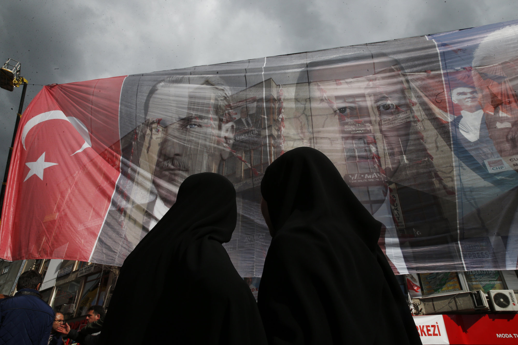Supporters of Turkey's President Recep Tayyip Erdogan, backdropped by banners of Turkish Republic founder Mustafa Kemal Ataturk, left, and Erdogan, right, leave a rally of the ruling Justice and Development Party, in Istanbul, Turkey, March 29. (AP Photo/Lefteris Pitarakis)