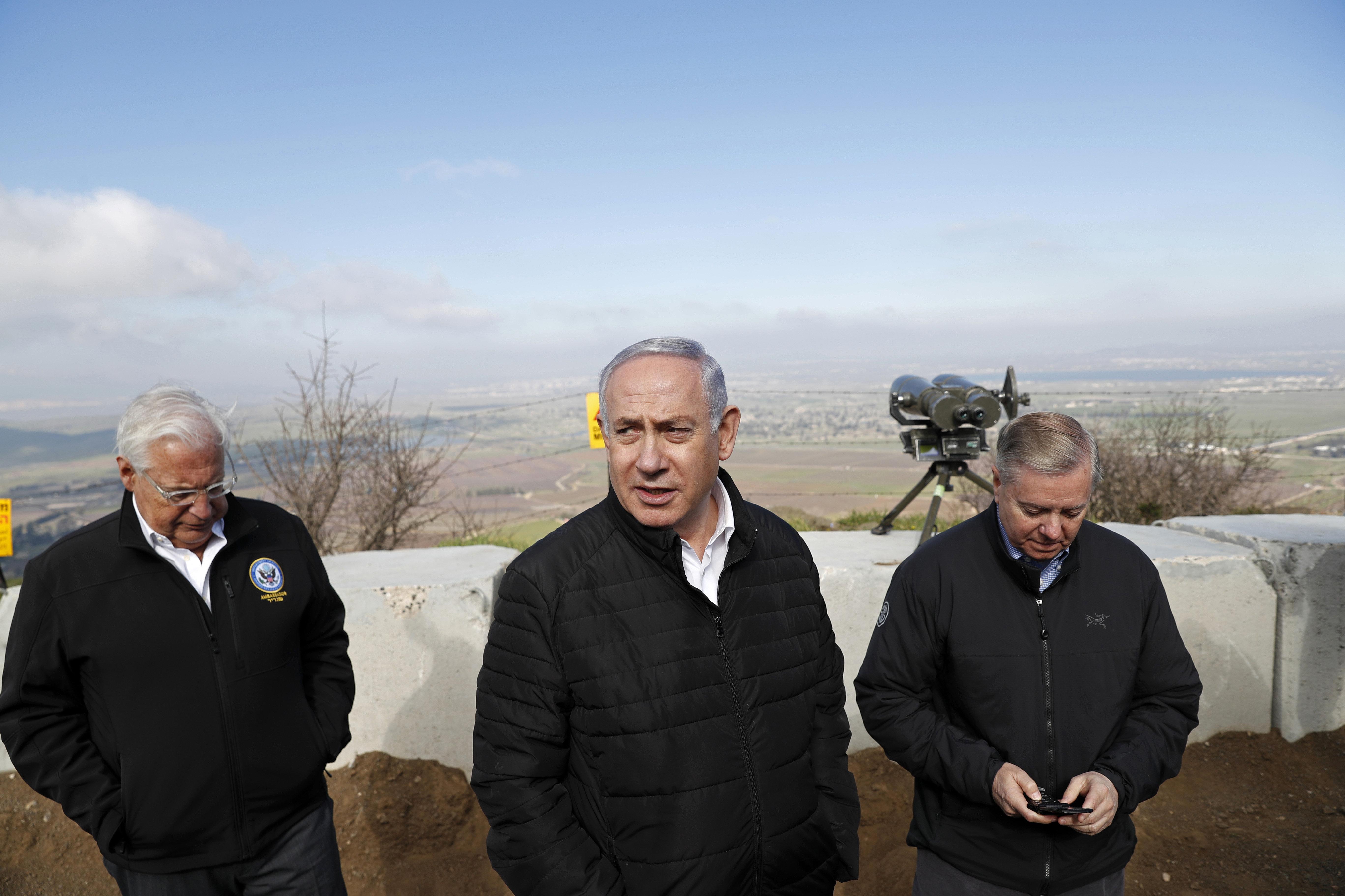 رئيس الوزراء الإسرائيلي بنيامين نتنياهو، في الوسط، والسيناتور الجمهوري ليندزي غراهام، في اليمين، والسفير الأمريكي في إسرائيل ديفيد فريدمان في زيارة للحدود بين إسرائيل وسوريا في منطقة الجولان التي تخضع للسيطرة الإسرائيلية، مارس/آذار 11. (رونين زفولون/بواسطة اسوشيتدبرس)