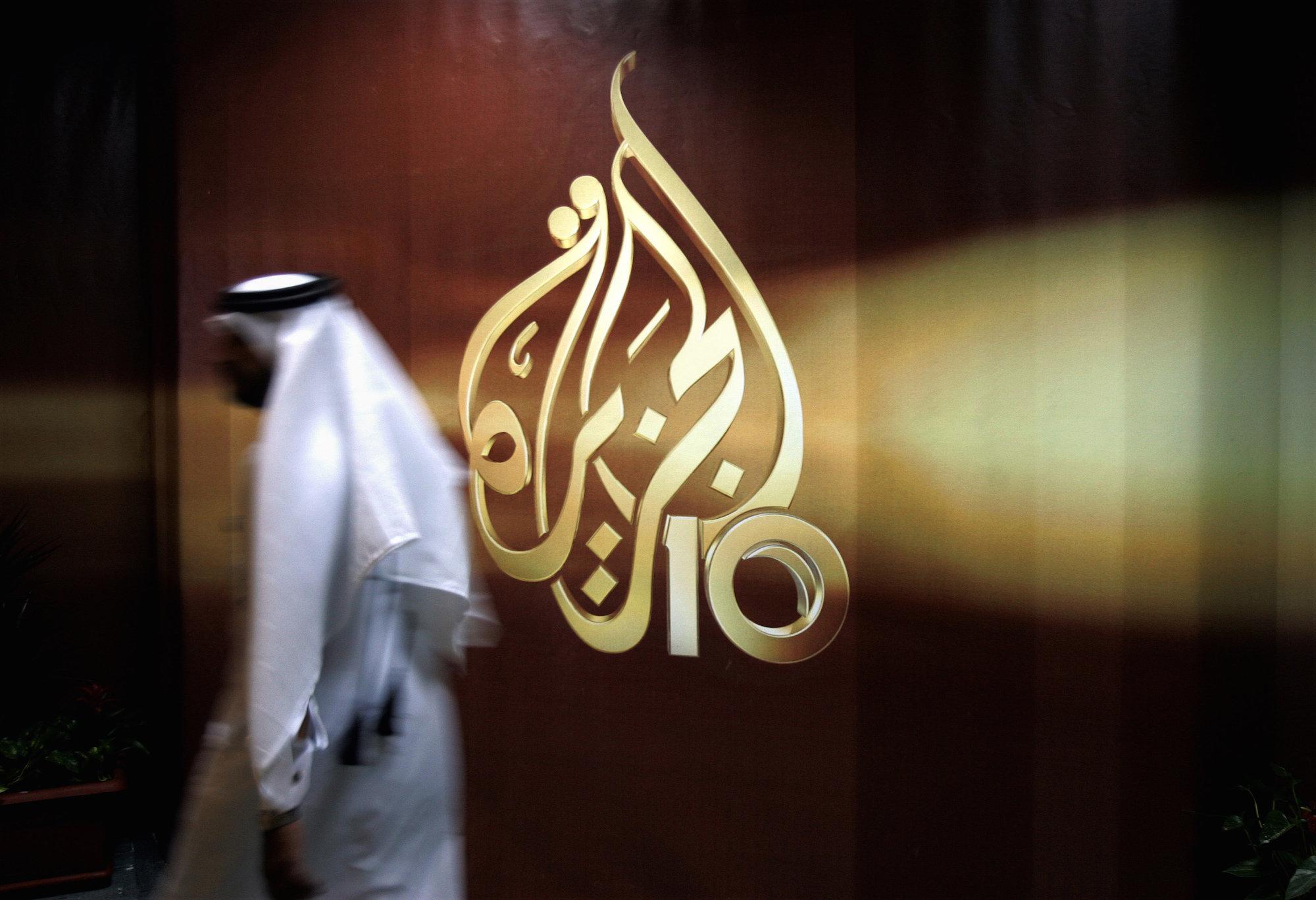 Man walks by Al Jazeera's Doha office