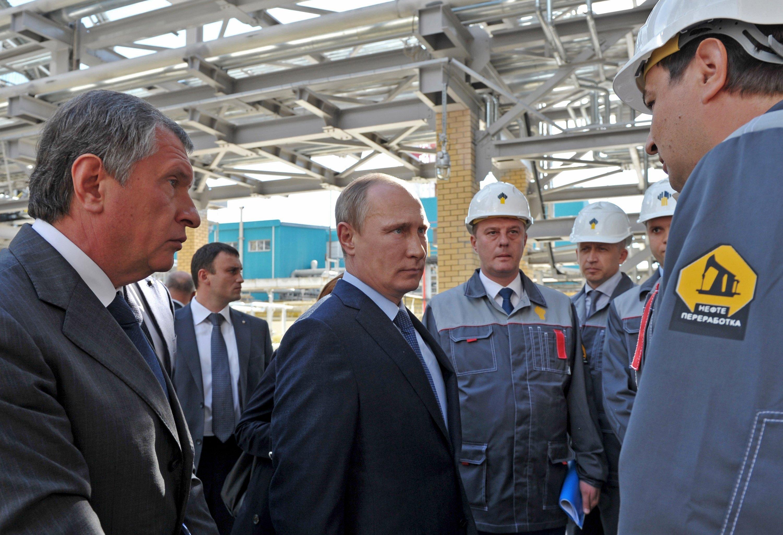 Russian President Vladimir Putin, center, and Igor Sechin, head of Rosneft, left, speak to workers while visiting the Rosneft oil refinery in the Black Sea port of Tuapse, Russia. (AP Photo/RIA-Novosti, Presidential Press Service, Alexei Nikolsky)