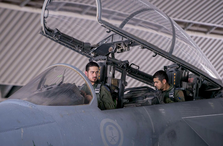 """طياران سعوديان يجلسان في قمرة القيادة على متن طائرة مقاتلة خلال الضربات الجوية التي نفّذها التحالف بقيادة الولايات المتحدة ضد تنظيم """"الدولة الإسلامية في العراق والشام"""" وأهداف أخرى في سوريا، في المملكة العربية السعودية في 24 أيلول/سبتمبر 2014 (الصورة من أسّوشييتد برس/وكالة الأنباء السعودية)"""