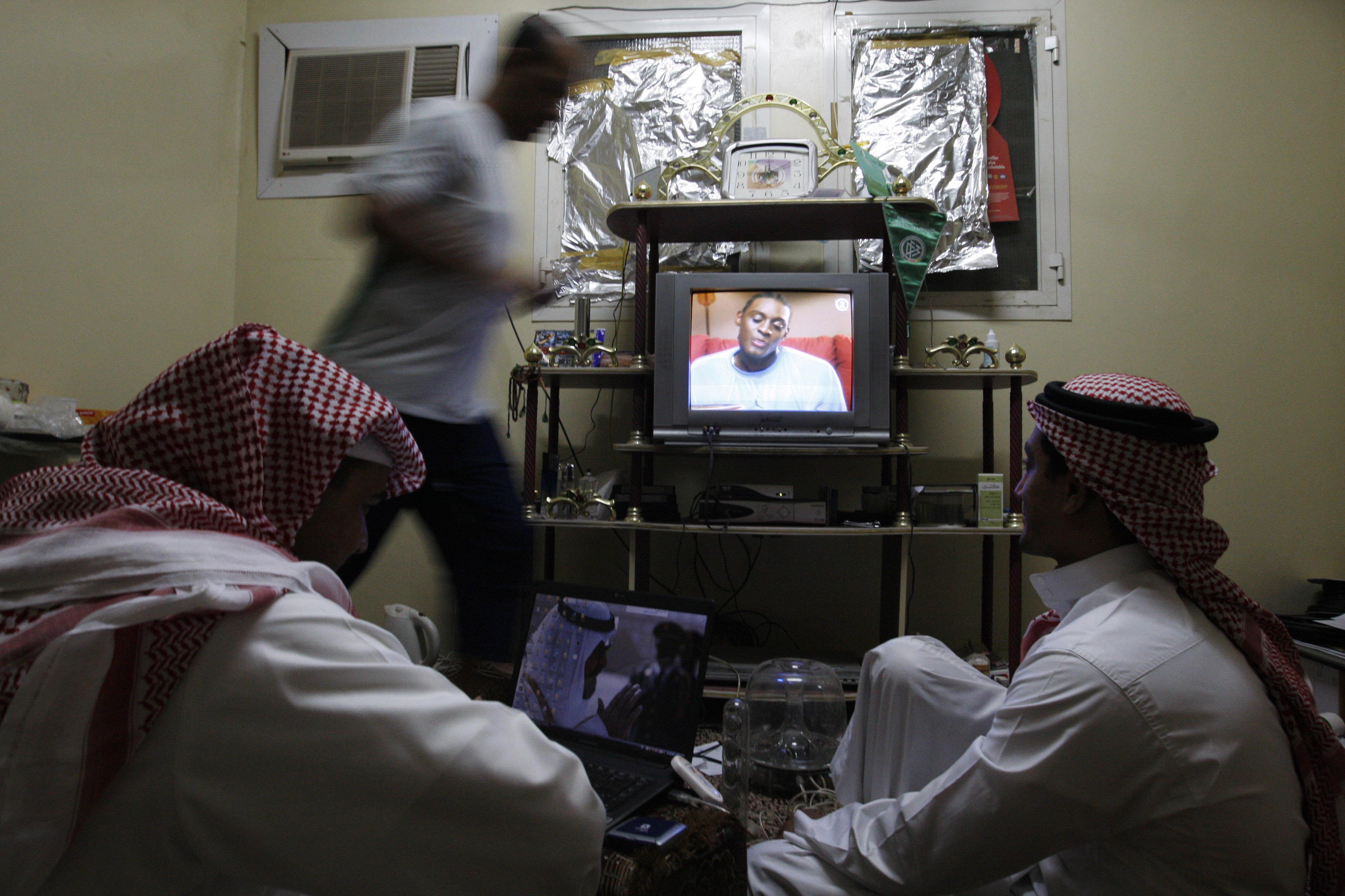 Saudi men watch satellite television at home in Riyadh, Saudi Arabia, Sept. 16, 2008. (AP Photo/Hassan Ammar)