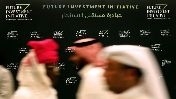 Participants walk in front of a banner for the Future Investment Initiative conference, in Riyadh, Saudi Arabia, Oct. 24, 2018. (AP Photo/Amr Nabil)