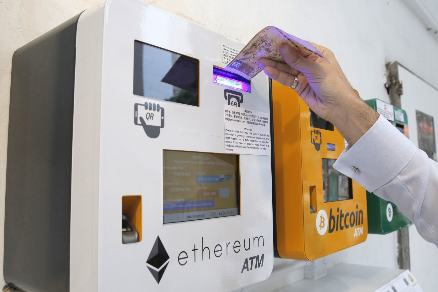 A man uses an Ethereum ATM, May 11, 2018. (AP Photo/Kin Cheung)