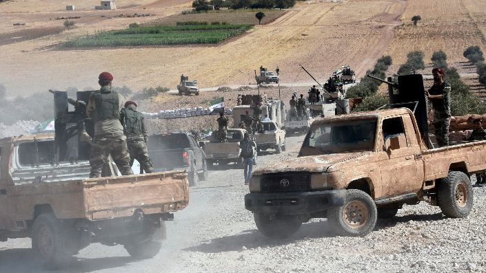 Turkish-backed Free Syrian Army fighters heading toward the Syrian town of Tal Abyad from the Turkish border town of Akcakale, Turkey, Oct. 10. (DHA via AP)