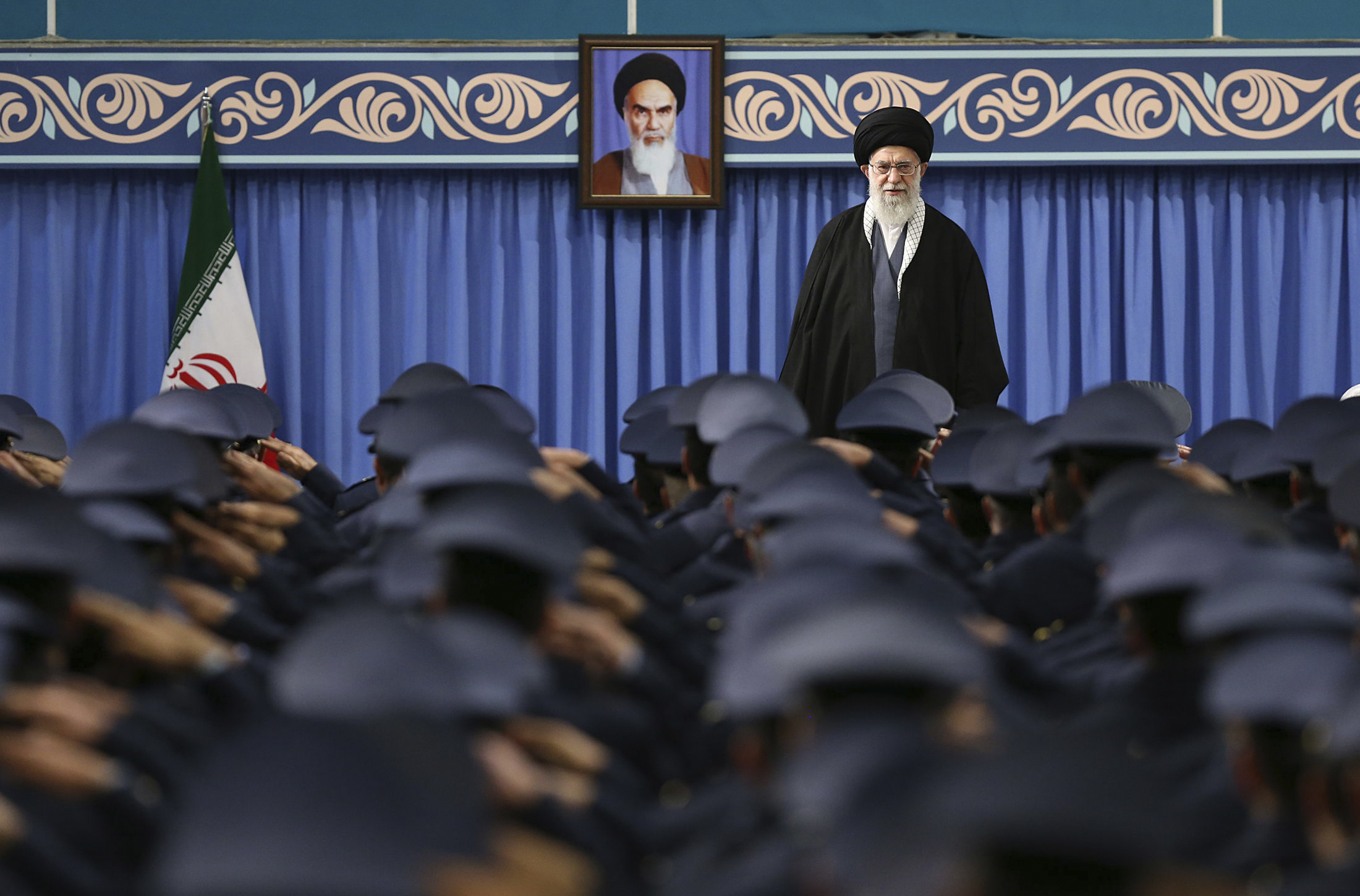 Iranian Supreme Leader Ayatollah Ali Khamenei stands as army air force and air defense staff salute at the start of their meeting in Tehran, Iran, Feb. 8, 2018. (Office of the Iranian Supreme Leader via AP)