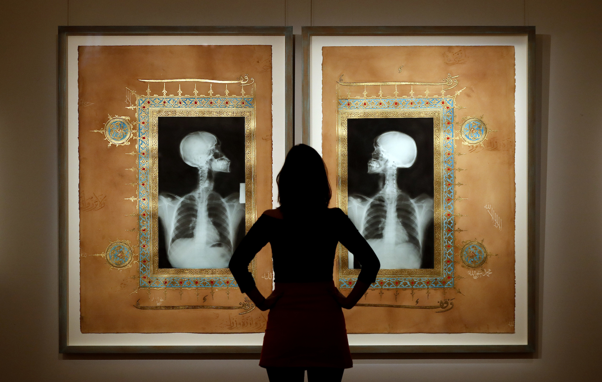 A woman looks toward artwork by Saudi artist Ahmed Mater on display at Sotheby's auction rooms in London, Oct. 13, 2016. (AP Photo/Kirsty Wigglesworth)
