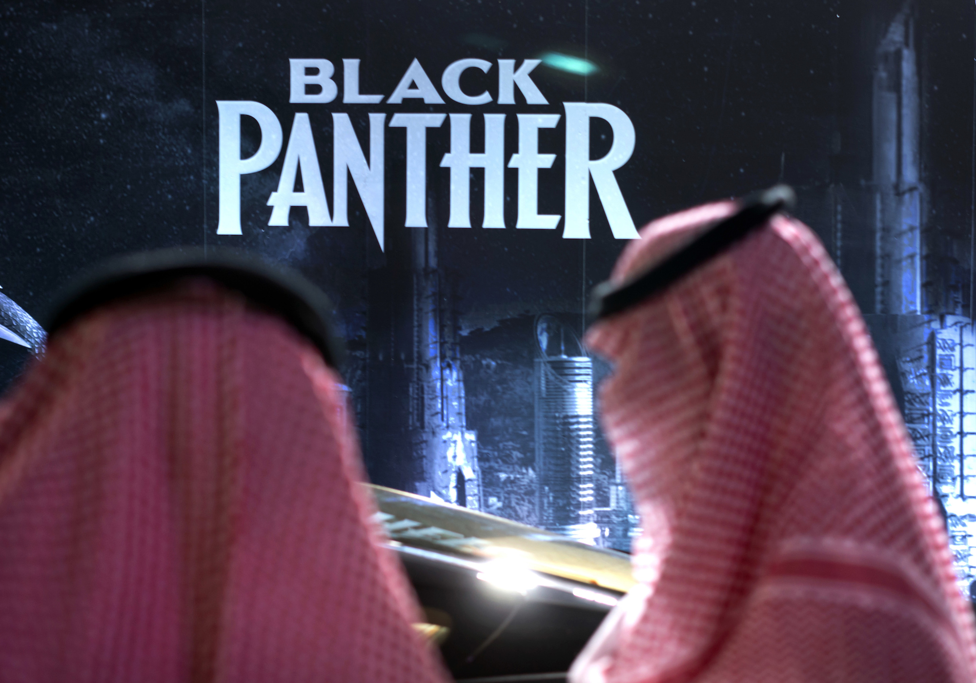 Saudis stand in front of poster for Black Panther