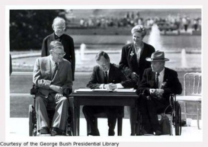 Signing of the Americans with Disabilities Act on July 26, 1990 at the White House. President George H.W. Bush sites at a table with the White House lawn and foundatin in the bakcground.  Two men in wheelchairs sit on either side of the table.  On the left a man stands and on the right a woman stands.